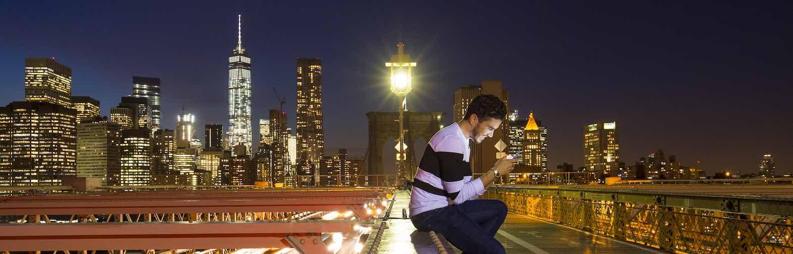 Man sitting on bridge at night